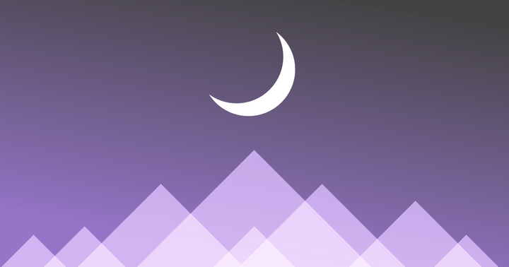 A moon hanging over mountains