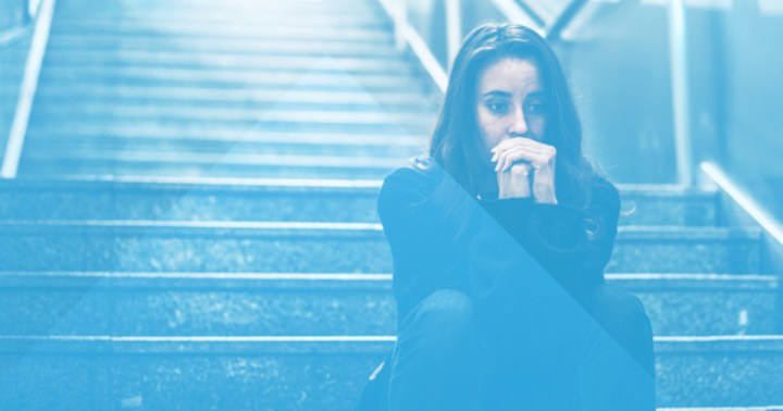 Woman sitting at the bottom of the stairs afraid to take the first steps to sobriety