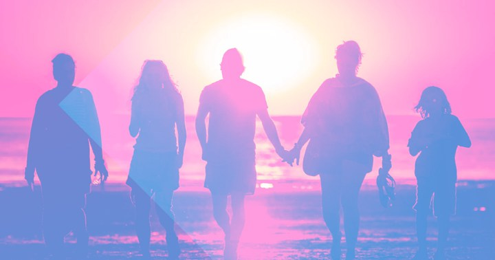 A family walking at the beach at sunset